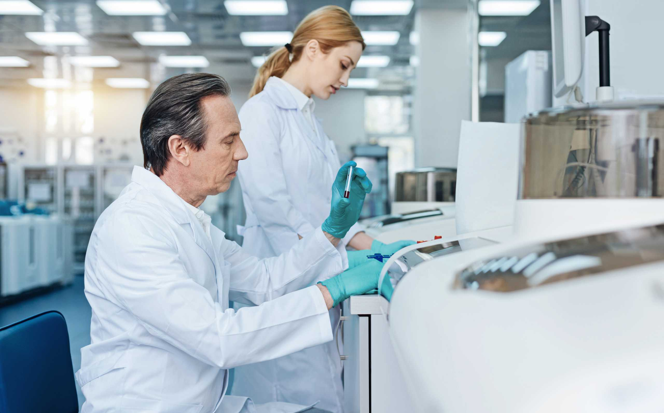 Laboratory assistants equiping analyzer with reagents